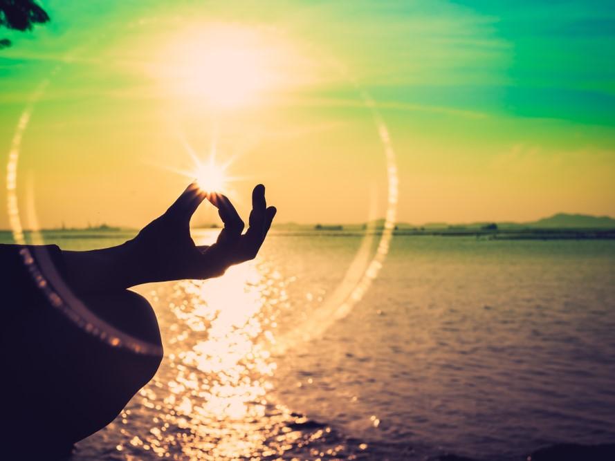 夕日の海辺でヨガポーズや蓮の位置を考える女性のシルエット