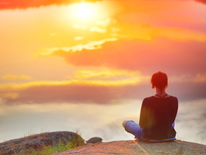 女性が山から夕日を見ている